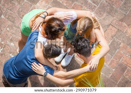 Group of teenagers embraced in circle, aerial view. They are two girls and two boys, looking each other - stock photo