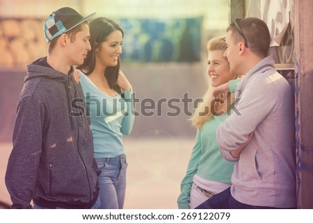Group of teenagers hanging out in the skate park or schoolyard - stock photo