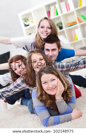 group of teenagers having fun indoor, smiling and looking at camera - stock photo