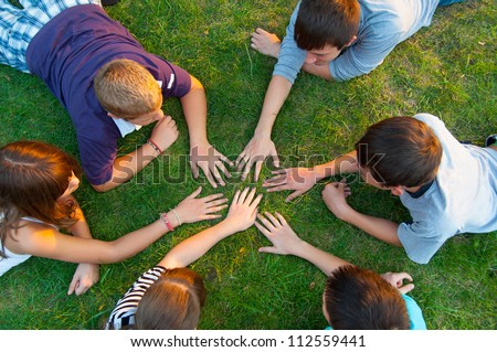 Group of teenagers having fun outdoor on beautiful summer day. - stock photo