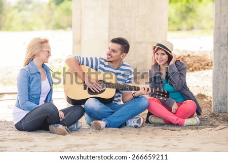 Group of teenagers having spring break party on the beach - stock photo