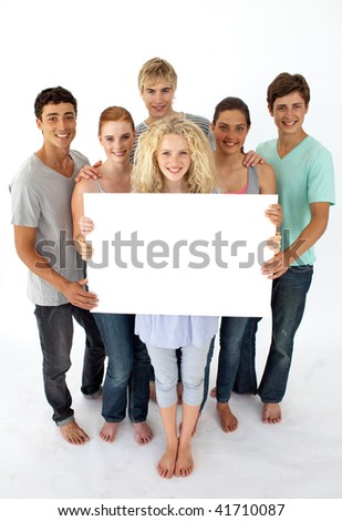 Group of teenagers holding a blank card agaisnt white background - stock photo