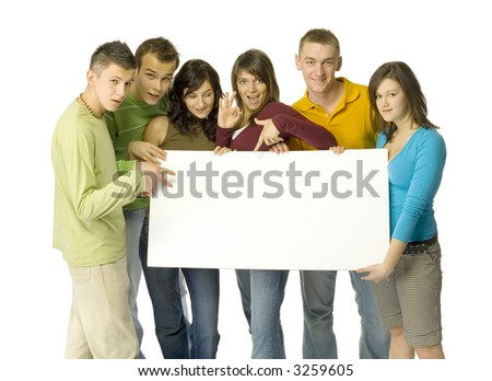 Group of 6 teenagers holding and pointing white blank board. They're looking at camera. White background behind them.