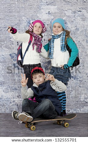 Group of teenagers in casual wear against a brick wall - stock photo