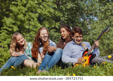 GRoup of teenagers in the park playing guitar and having fun