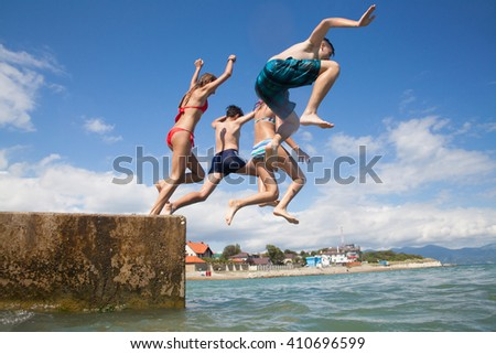 Group of teenagers jumping off the pier into the sea. fun summer vacation - stock photo
