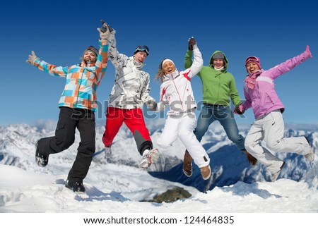 Group of  teenagers jumping together in winter resort in Alps