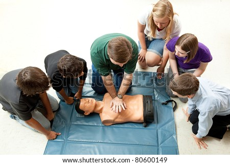 Group of teenagers learing CPR (cardiopulmonary resuscitation) in school. - stock photo