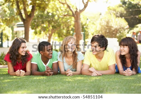 Group Of Teenagers Lying On Stomachs In Park - stock photo
