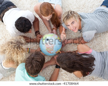 Group of teenagers lying on the floor examining a terrestrial world and a guy with thumb up - stock photo