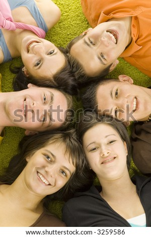 Group of 6 teenagers lying on the floor head next to head. They're looking at camera and smiling. - stock photo