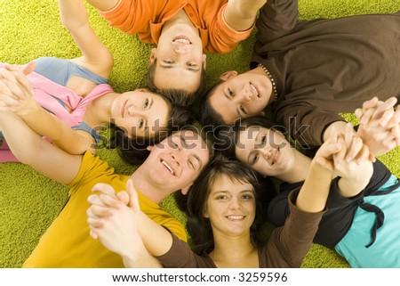 Group of 6 teenagers lying on the floor head next to head. They're looking at camera and smiling. They're holding their hands up. - stock photo