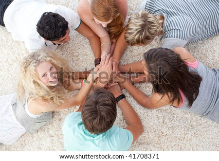 Group of teenagers lying on the floor with hands together - stock photo