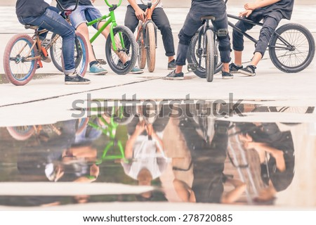 group of teenagers on a bikes at outdoor, freestyle park with reflection for copy space - stock photo