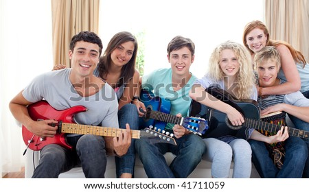 Group of teenagers playing guitar at home together - stock photo