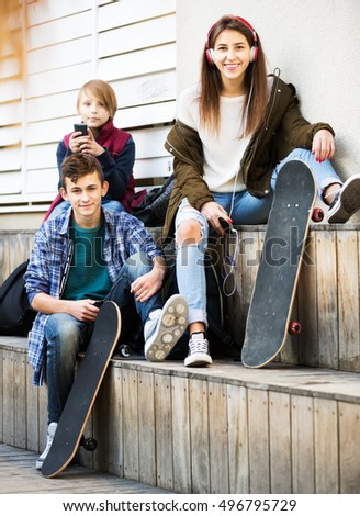 Group of teenagers relaxing with mobile phones outdoor