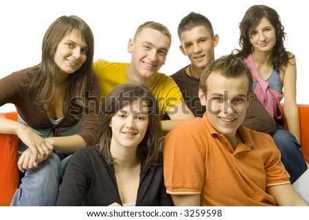 Group of 6 teenagers sitting on and next to the red couch. They're smiling and looking at camera. - stock photo