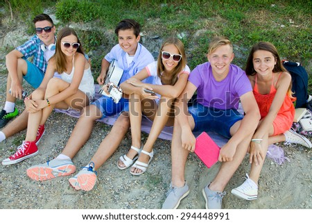 group of teenagers spending time together with guitar