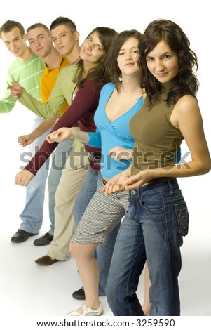 Group of 6 teenagers standing in line. They're looking at camera and dancing.