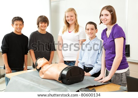 Group of teenagers with a CPR training dummy, about to learn cardiopulmonary resuscitation. - stock photo