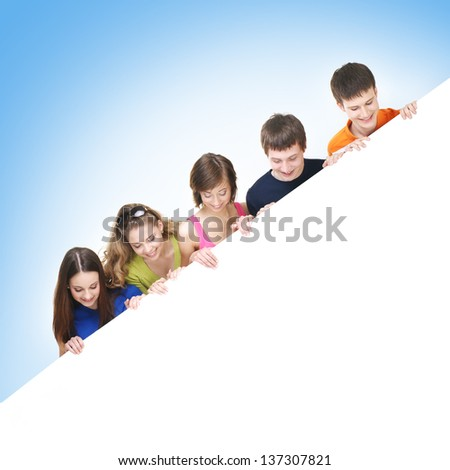 Group of teenagers with a giant, blank, white billboard over blue background - stock photo