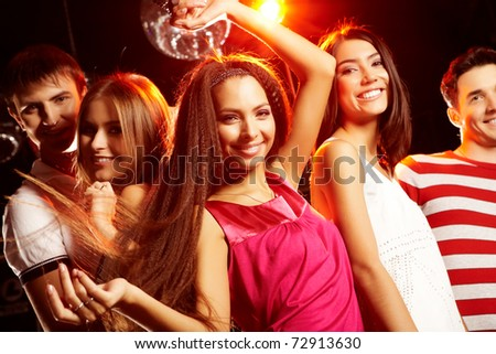 Group of teens dancing in night club with glamorous girl in front