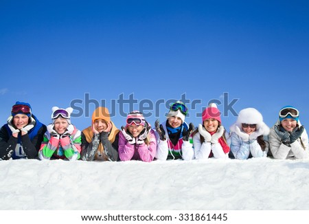 Group of teens lying on snow in ski resort