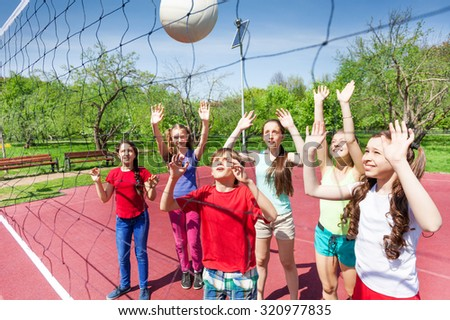 Group of teens playing volleyball near the net on the court during sunny summer day outside - stock photo