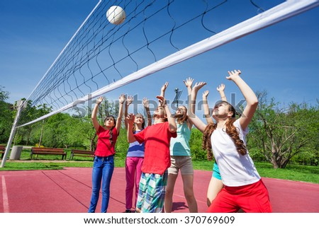 Group of teens with arms up play volleyball - stock photo
