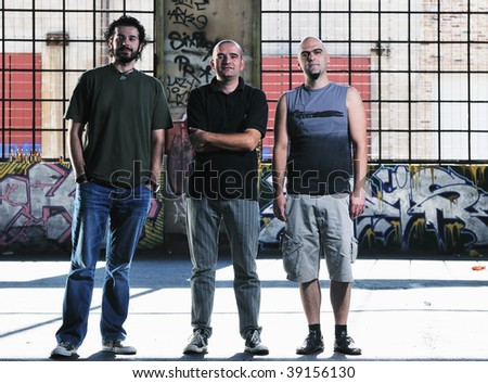 group of three adult man outdoor in the city at the sunset representing urban and modern everyday scene - stock photo