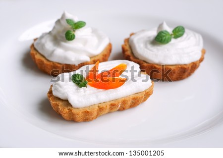 Group of three baked home-made cupcakes with cream, decorated with apricot slices and leaves of mint, served on white plate