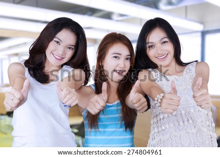 Group of three beautiful girls standing in the classroom while showing thumbs up gesture - stock photo