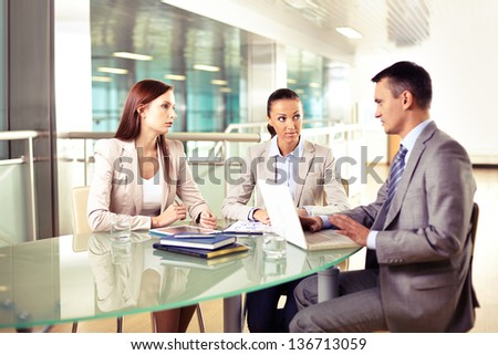 Group of three business partners interacting at meeting in office - stock photo