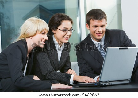Group of three business people looking at monitor - stock photo