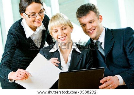 Group of three business people looking at monitor of laptop - stock photo
