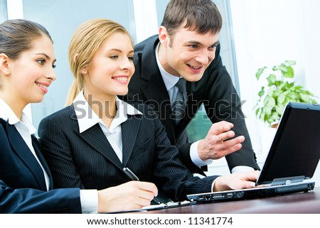 Group of three business people working on the laptop