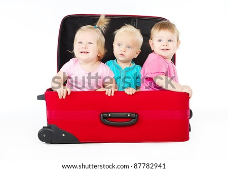 group of three children sitting inside big red suitcase over white background - stock photo