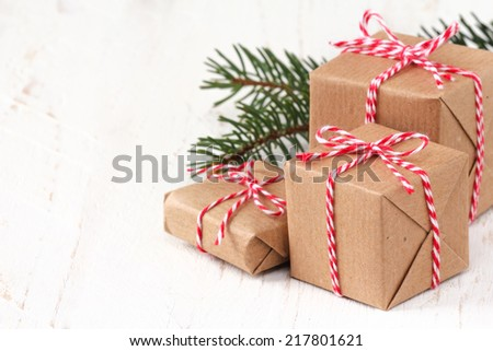 Group of three Christmas presents wrapped in brown paper and ties with a festive red and and white baker's twine on white wooden background with copy space - stock photo