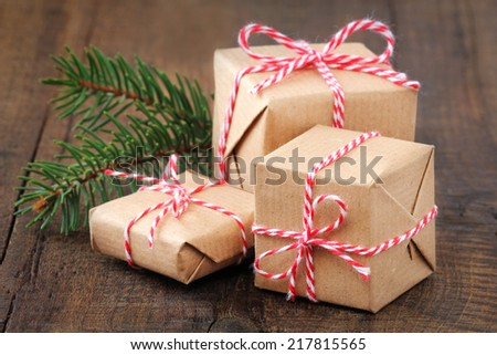 Group of three Christmas presents wrapped in brown paper and ties with a festive red and and white baker's twine on dark wooden background - stock photo