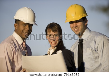 Group of three co-workers outdoors looking at blueprints. - stock photo