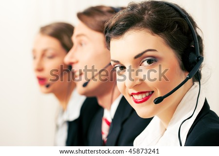 Group of three customer care representatives in a call center with headphones rendering service to callers