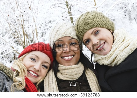Group of three diverse young girl friends outdoors in winter - stock photo