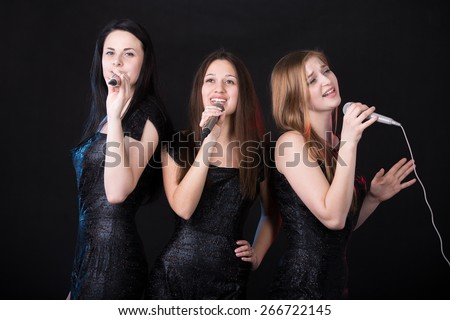 Group of three emotional beautiful young female singers with microphones singing, girls band concert - stock photo
