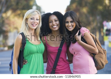 Group of three female friends having fun off campus - stock photo