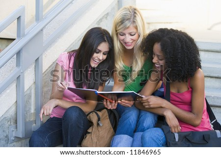 Group of three female students sitting on steps - stock photo