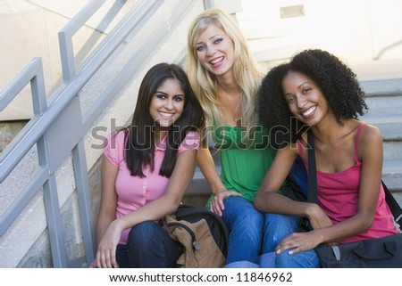 Group of three female university students sitting on steps - stock photo