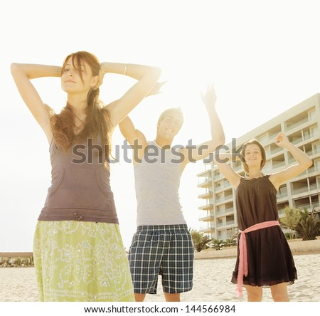 Group of three friends dancing, listening to music and having fun on an urban beach in the city with their arms up against the sunshine filtering trough them.