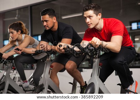 Group of three friends doing some cardio on a bicycle at a gym and concentration on their workout - stock photo
