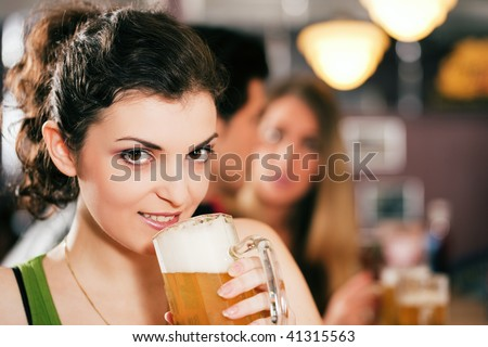 Group of three friends in a bar drinking beer - selective focus on beautiful woman in front zipping from her glass