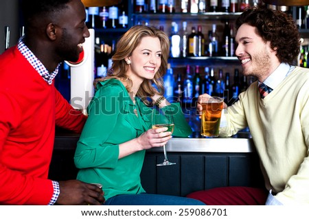 Group of three friends in a bar having drinks